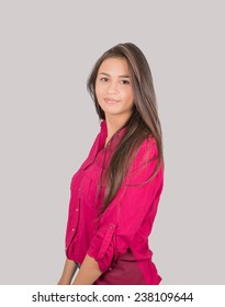 Young Latin Girl, wearing a pink shirt, standing and looking at the camera. Isolated on gray.