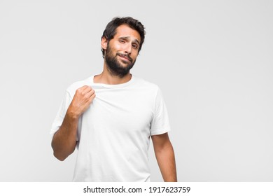 young latin handsome man looking excited and surprised pointing to the side and upwards to copy space