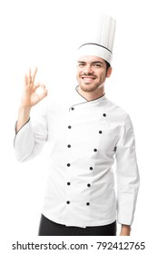 Young Latin male chef in uniform making an okay sign with his hand and smiling