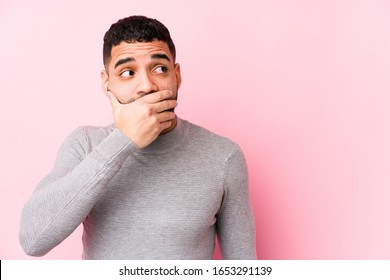 Young latin man against a pink background isolated thoughtful looking to a copy space covering mouth with hand.