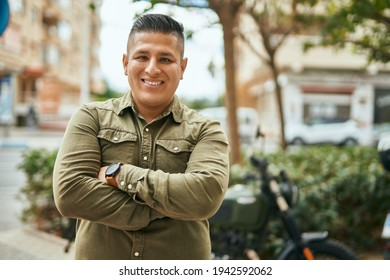 Young latin man with arms crossed smiling happy at the city.