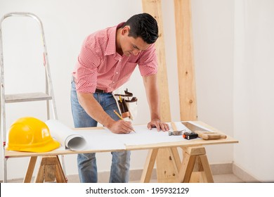 Young Latin man drawing and modifying a house design