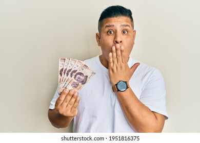 Young latin man holding 500 mexican pesos banknotes covering mouth with hand, shocked and afraid for mistake. surprised expression