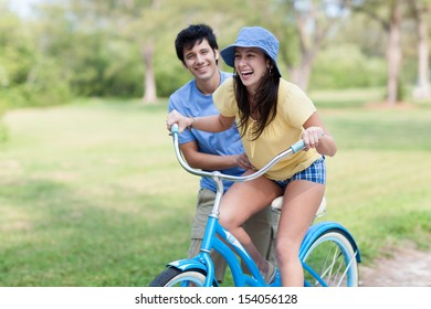 Young latin man in shorts and blue shirt helps young woman riding blue bike with green trees and grass. Horizontal shallow focused composition.