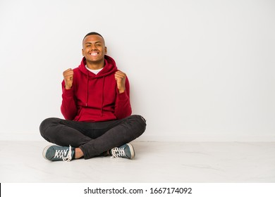 Young latin man sitting on the floor isolated cheering carefree and excited. Victory concept.