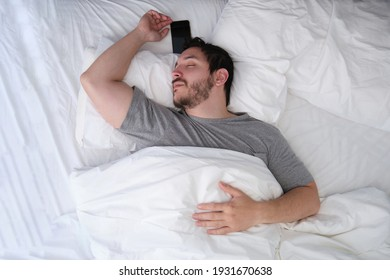 Young latin man sleeping spread out in bed with his smartphone. Sleep position concept.