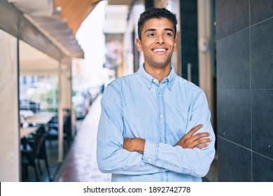 Young latin man smiling happy walking at the city.
