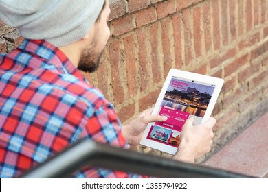 Young latin man with tablet booking a hotel on application. Travel and media concept. All screen graphics are made up by us