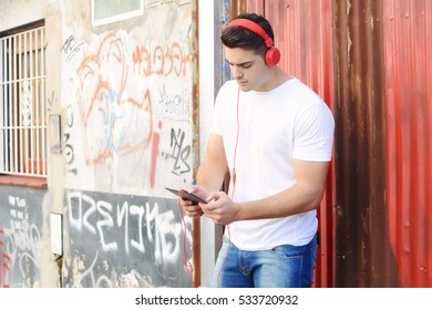 Young latin man using a tablet with headphones on the street.