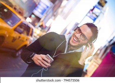 Young latin man walking in New York with headphones and smart phone