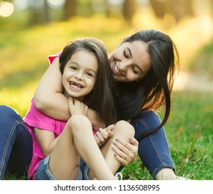 Young latin mother and daughter laughing in city park