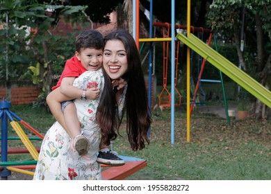 Young latin mother has fun with her son in a park child happy mother happy mother's day