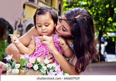 Young latin mother is playing with her daughter with a basket full of plastic flowers.