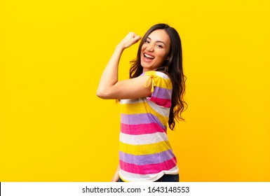 young latin pretty woman feeling happy, satisfied and powerful, flexing fit and muscular biceps, looking strong after the gym against flat wall