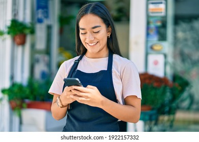 Young latin shopkeeper girl smiling happy using smartphone at florist.