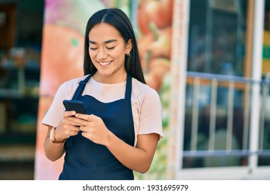 Young latin shopkeeper girl smiling happy using smartphone at fruit store.