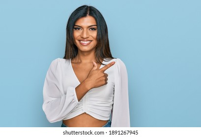 Young latin transsexual transgender woman wearing casual clothes cheerful with a smile on face pointing with hand and finger up to the side with happy and natural expression