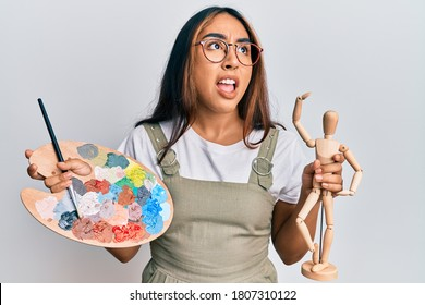 Young latin woman artist holding palette and manikin angry and mad screaming frustrated and furious, shouting with anger. rage and aggressive concept.