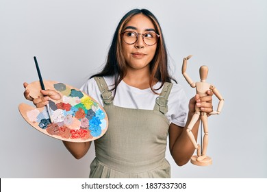 Young latin woman artist holding palette and manikin smiling looking to the side and staring away thinking.