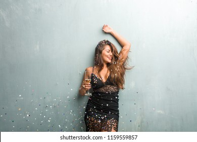 Young latin woman celebrating new year or an event. Excited and happy, holding a champagne bottle and a cup.