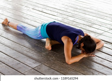 Young latin woman doing yoga relaxing pose. Resting on the floor. Pigeon yoga pose on a tropical beach area.