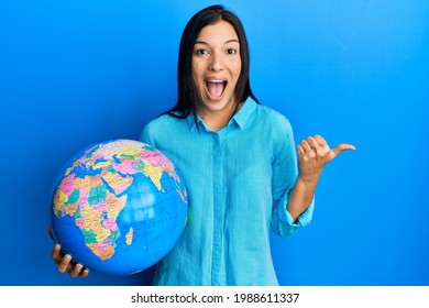 Young latin woman holding big world ball pointing thumb up to the side smiling happy with open mouth