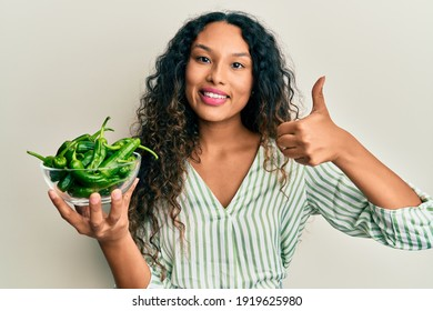 Young latin woman holding bowl with green peppers smiling happy and positive, thumb up doing excellent and approval sign