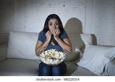 young latin woman at home sofa couch in living room watching television scary horror movie or suspense thriller film or horrible news horrified holding remote controller in panic eating popcorn bowl