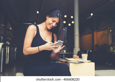 Young latin woman making self portrait on her smart phone digital camera while sitting in sidewalk cafe during lunch break. Pretty female posing while photographing herself for social network picture