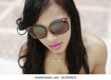 Young latin woman in pink dress with sunglasses