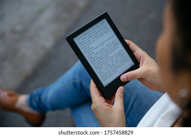 young latin woman reading an e book on digital tablet device. Focus on the ebook.