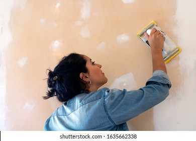 Young latin woman smooths a plastering indoor wall with sandpaper