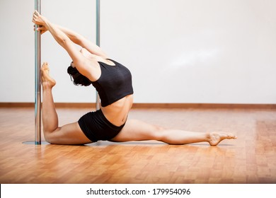 Young Latin woman stretching and warming up for her pole fitness class