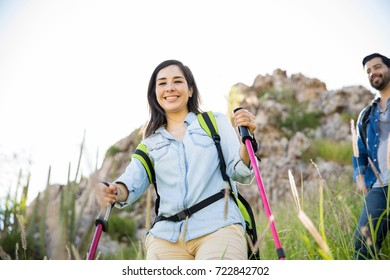 Young Latin woman with trekking poles walking on a mountain with her boyfriend and having a good time