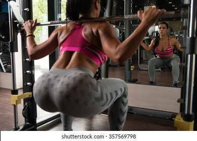 Young Latin Woman Working Out Legs With Barbell In Fitness Center - Squat