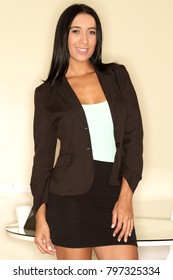 Young Latina businesswoman in suit smiling at her office