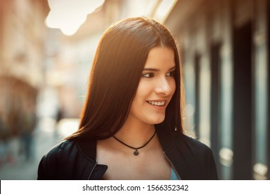 """young Latina with long hair, on """"Krämerbrücke"""" in Erfurt, Germany, sightseeing, while the sun is setting"""