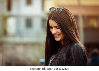 young Latina with long hair and sunglasses on her head, smiling and looking down, in an urban environment