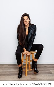 young Latina with long hair, wearing a leather jacket, posing on a wooden stool, with white background and wooden floor