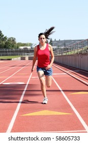 Young latina teen girl running on track shorts red top