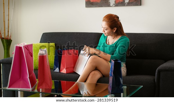 Young latina woman back at home after shopping, surrounded by bags on sofa. She peeps into a bag reviewing her new purchase