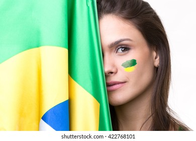 Young latina woman covering half her face on Brazilian flag
