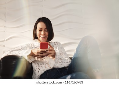 Young latina woman messaging with mobile telephone on sofa at home. Happy hispanic girl with cell phone. People using smartphone for texting message