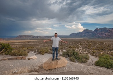 A young latino american standing on a rock and posing for the camera with the Red Rock Canyon landscape and rolling clouds behind him.