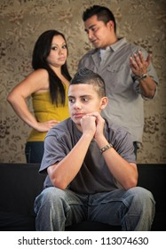 Young Latino boy in blank stare with concerned parents behind him