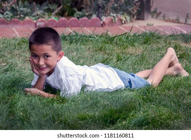 Young latino boy laying in the grass