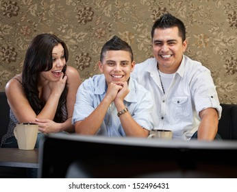 Young Latino family enjoying television indoors together