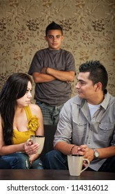 Young Latino family with stubborn son in background