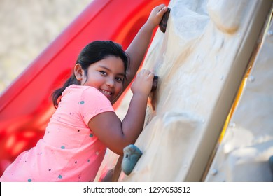 Young latino girl climbing a playground wall and smiling.