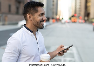 Young Latino Hispanic man in city walking texting cell phone